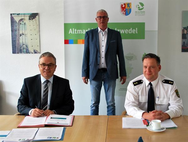 Bild_(c)_AMK: Landrat Michael Ziche unterzeichnet das Sicherheitskonzept unter den Blicken von Dezernatsleiter II Hans-Dieter Thiele und Revierleiter der Polizei Sebastian Heutig